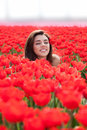 Beauty young woman with flowers tulips on the meadow red outdoors Royalty Free Stock Photography