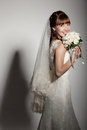 A beautyful bride holding her bouquet from roses and smiling dark background Royalty Free Stock Photography