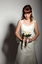 A beautyful bride looks down at her bouquet from roses dark background Stock Photography