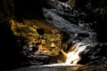 Beautyful Mystery night yellow light at deep tropical rain forest with flowing cascade waterfall Royalty Free Stock Photo