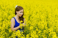 Beautyful teeny model in canola field teenager beauty with blue dress Royalty Free Stock Photos