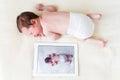 Bebê recém nascido ao lado de sua foto em um pc da tabuleta Fotografia de Stock