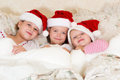 In bed with christmas hats little girls wearing red santa Stock Photo