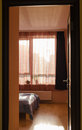 Bed illuminated by sunlight window curtains Royalty Free Stock Photo
