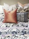 Bed with lots of colorful pillows close up a Royalty Free Stock Photography