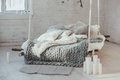 The bed suspended from the ceiling. Grey big cozy blanket knit. Scandinavian style, gray plaid, candles. Royalty Free Stock Photo