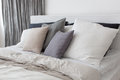 Bed with white and grey linens Royalty Free Stock Photo