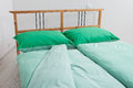 Bedding in green and white incrustation on bed chequered Stock Image