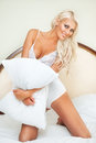 Bedroom beautiful blonde woman pose with pillow in bed Royalty Free Stock Image