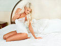 Bedroom elegant blonde woman sitting in bed Royalty Free Stock Images