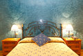 Bedroom hotel with two wooden bedside tables two lamps iron headboard and blue stone wall Royalty Free Stock Image