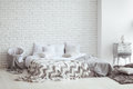 Bedroom interior with a brick wall with a bed and bedside tables Royalty Free Stock Photo