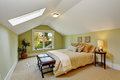Bedroom interior with vaulted ceiling and light mint walls white skylight room has queen size bed ottoman table Stock Photos