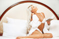 Bedroom romantic young blonde woman with book in bed at Stock Photography