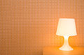 Bedside table lamp with orange wallpaper Stock Photo