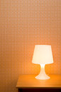 Bedside table lamp with orange wallpaper Royalty Free Stock Photography