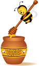Bee carrying a wooden honey spoon Royalty Free Stock Photo