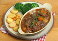 Beef bourguignon stew dinner served with roast potatoes and broccoli Stock Photo