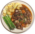 Beef bourguignon stew with vegetables new potatoes and asparagus Stock Photo