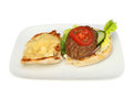 Beef burger with salad and cheese on toasted ciabata bread on a plate isolated against white Stock Images
