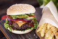 Beef burgers on a wooden board with chips and aromatic spices. Royalty Free Stock Photo
