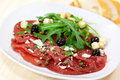 Beef carpaccio with pepper, rucola and parmesan Royalty Free Stock Photography