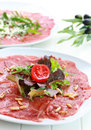 Beef carpaccio with rucola and pine nuts Stock Image