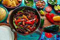 Beef fajitas in a pan sauces chili and sides mexican with food Royalty Free Stock Images
