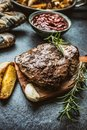 Beef grilled steaks with barbecue sauce roasted potatoes and rosemary Royalty Free Stock Photo
