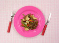 Beef meal pink plate plaid tablecloth a and vegetable on a bright and Royalty Free Stock Images