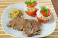 Beef steak with fried onion and stuffed vegetables close up on a dish a two tomatoes Royalty Free Stock Image