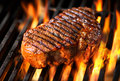Beef steak on the grill with flames Royalty Free Stock Photography