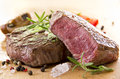 Beef steak with herbs as closeup on a wooden plate Stock Photography