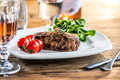 Beef Steak. Juicy beef steak. Gourmet steak with vegetables and glass of rose wine on wooden table Royalty Free Stock Photo