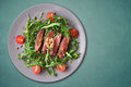 Beef steak medium ruccola salad with tomatoes and walnuts gray plate blue background copy space Royalty Free Stock Photos