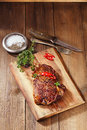 Beef steak with red chillies on wood and table old Royalty Free Stock Images