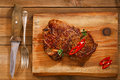 Beef steak with red chillies on wood and table wooden Stock Images