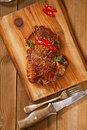 Beef steak with red chillies on wood and table wooden board Royalty Free Stock Photography