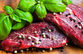 Beef steak on wooden board with basil Royalty Free Stock Photo