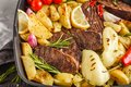 Beef steaks grilled with baked potatoes and vegetables in a pan Royalty Free Stock Photo