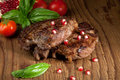 Beef steaks pan seared with fresh tomatoes basil and pomegranate Stock Photo