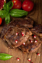 Beef steaks pan seared with fresh tomatoes basil and pomegranate Royalty Free Stock Photos