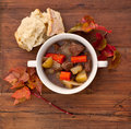 Beef stew with bread and leaves on a weathered wooden table Stock Image
