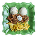 Beef stroganov beef stroganoff with fries rice and mushrooms on the green plate Royalty Free Stock Photo
