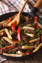 Beef with vegetables lomo saltado close up in a pan vertical and fries frying Stock Images