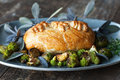 Beef wellington golden with purple sage and roasted vegetables Stock Photo