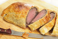 Beef wellington sliced with knife a or boeuf en croute on a wooden chopping board a carving Stock Photos
