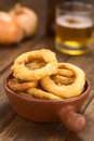 Beer battered onion rings freshly prepared homemade in a rustic bowl with in the back selective focus focus on the front of Royalty Free Stock Image