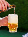 Beer from a beer bottle beer glass is poured Royalty Free Stock Image