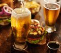 Beer being poured into glass with gourmet hamburgers in background Royalty Free Stock Photo